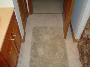 Bathroom ceramic tile floor with floor rugs.