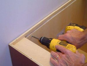 Secure bathroom vanity to the bathroom wall with screws.