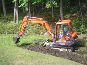 Landscaping backyard with a backhoe.