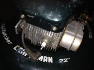 Clean spark plug as part of spring maintenance on lawnmower