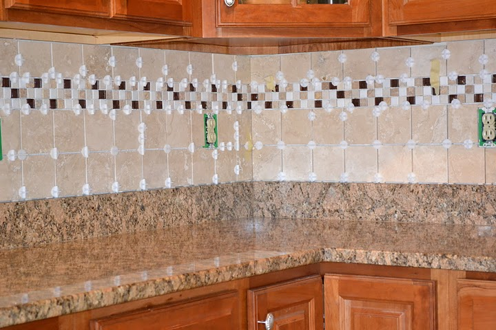 freshly tiled kitchen backsplash with spacers still installed