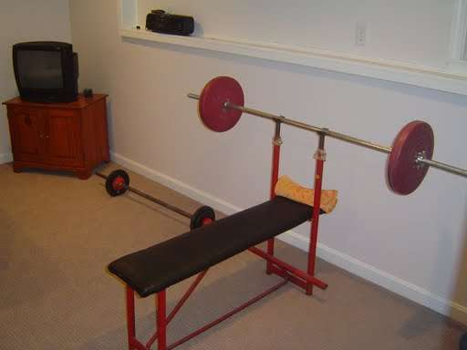 A workbench and free weights in a Basement Home Gym