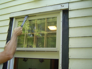 Removing old exterior window trim.