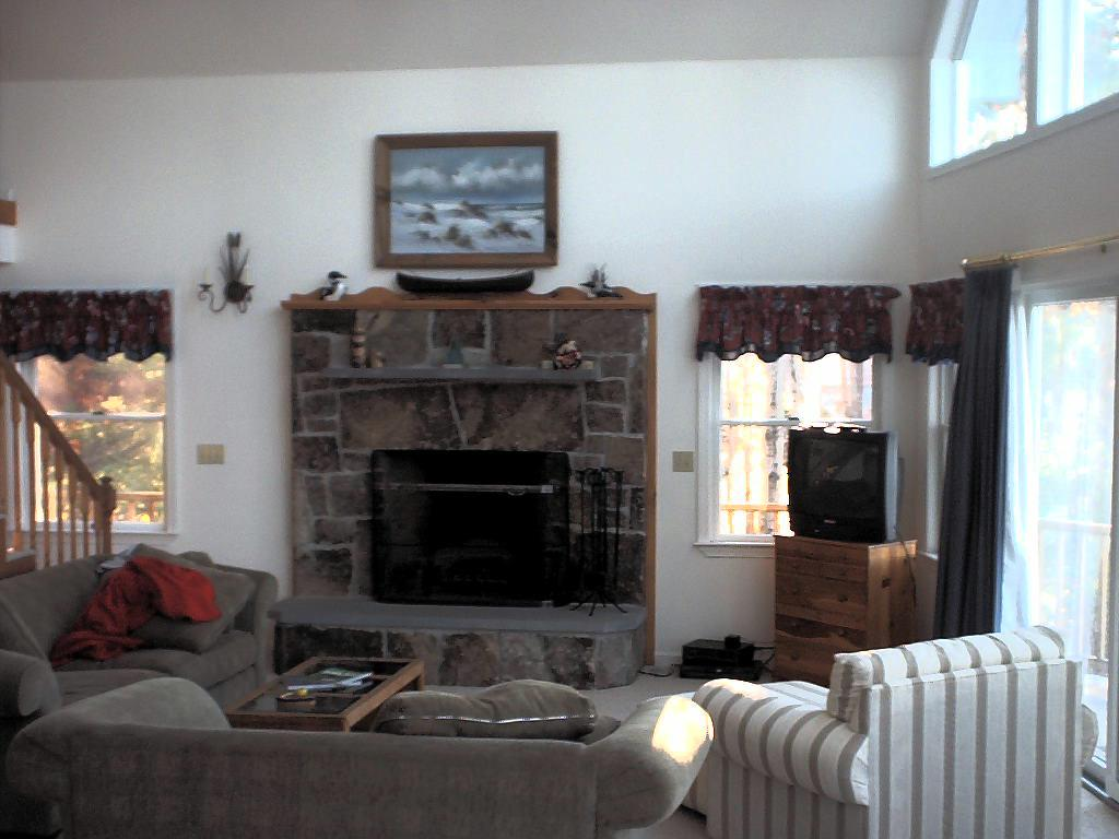 Large living room with a valuted ceiling and stone fireplace.